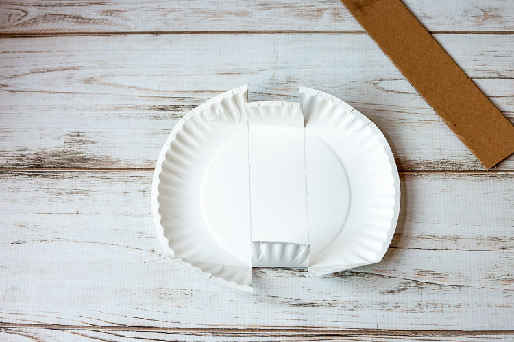 Paper plate cut along drawn lines until they meet the inner circle and folded up next to a piece of cardboard.