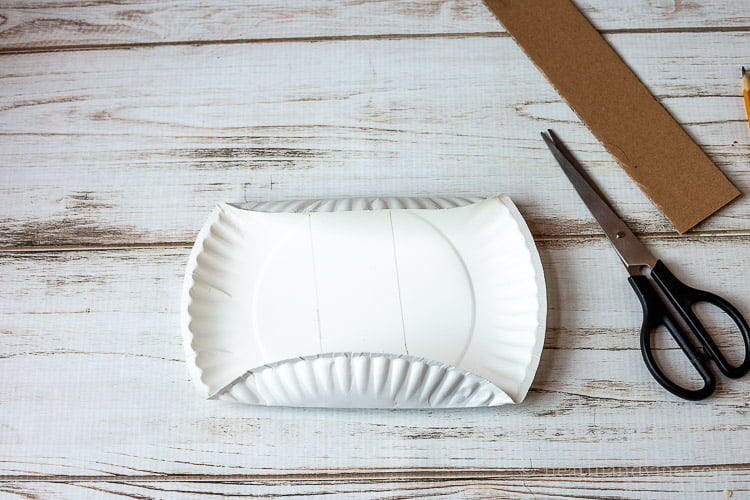 Paper plate folded on the bottom and top next to scissors and a 2 inch cardboard strip.