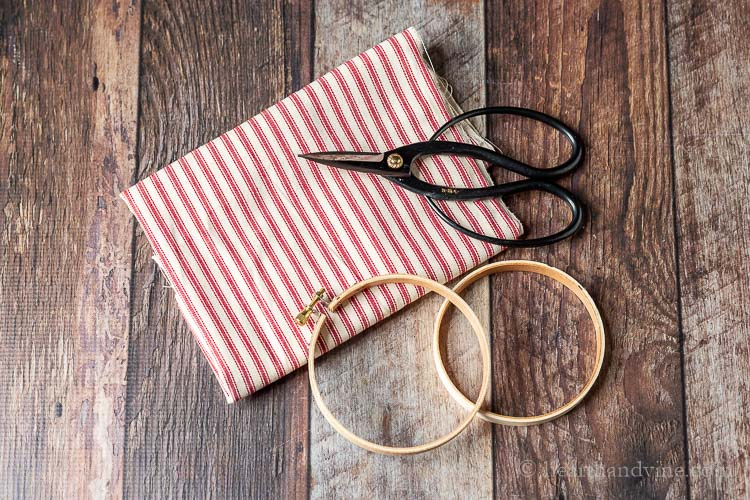 Red and white ticking fabric, mini wooden embroidery hoop and black scissors.