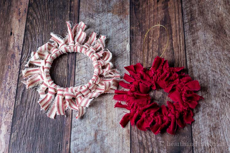 Two mini rag wreath ornaments. One is red and white striped and the other all dark red.