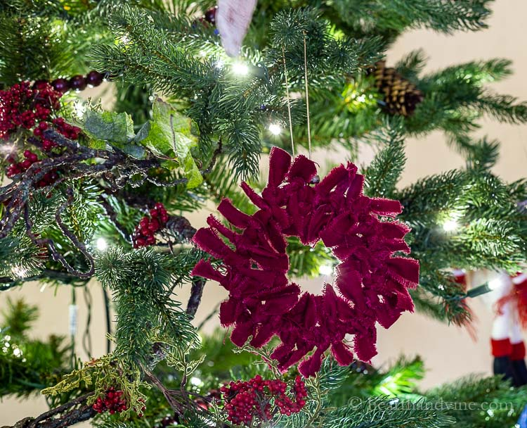 Dark red rag wreath ornament hanging on the tree.