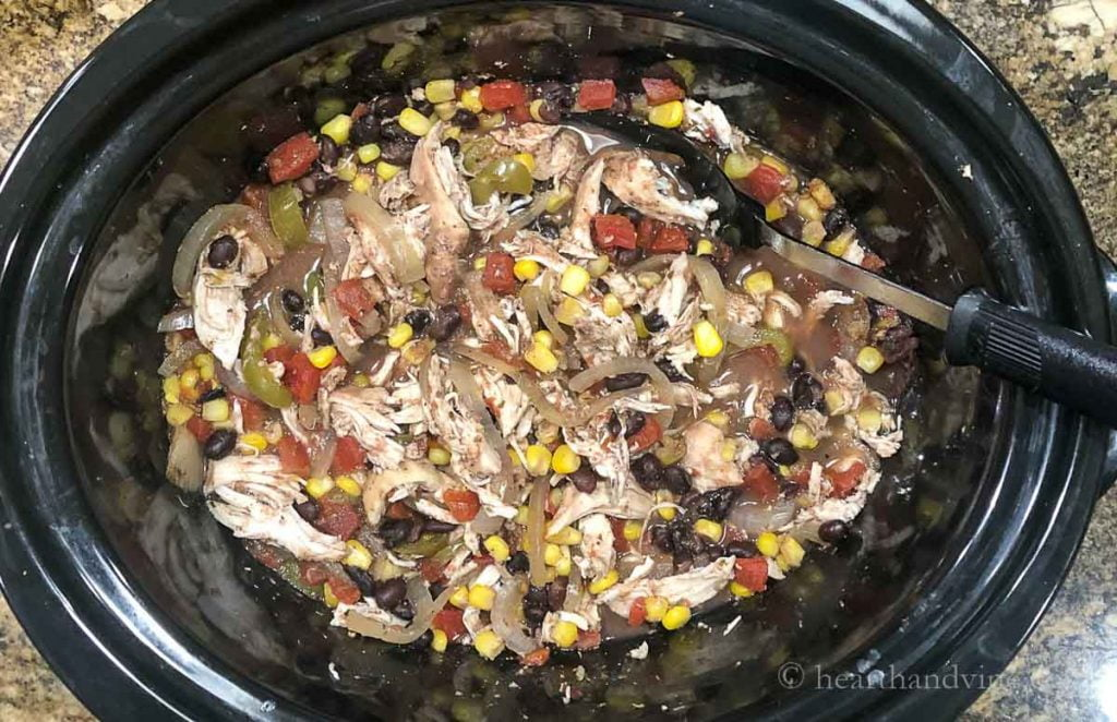 Slow cooker and spoon with shredded chicken, black beans, corn, vegetables and spices.