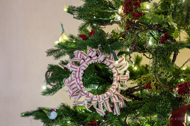 Red and white striped fabric ornament hanging on the Christmas tree.