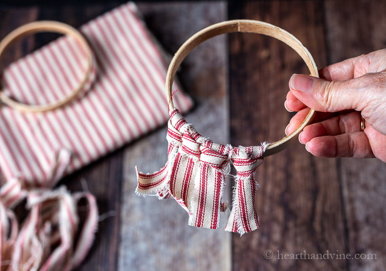 Pieces of red and white fabric tied onto an embroidery hoop.