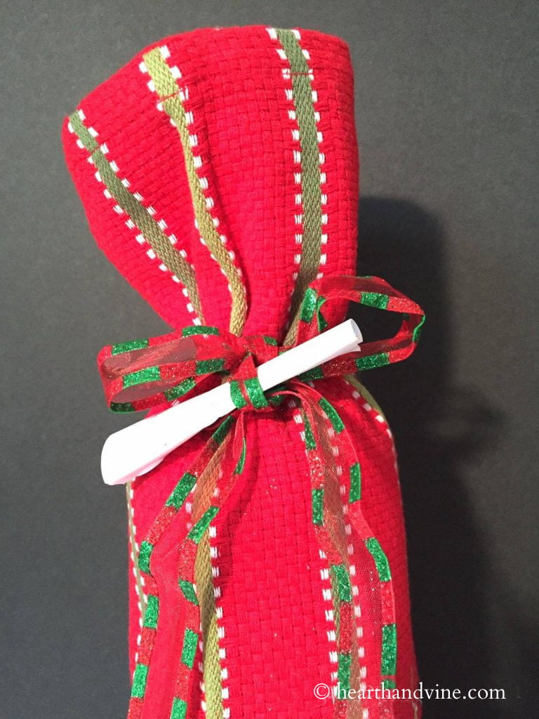 Bottle of wine wrapped in a Christmas tea towel. A small scroll of paper in tucked into the bow.