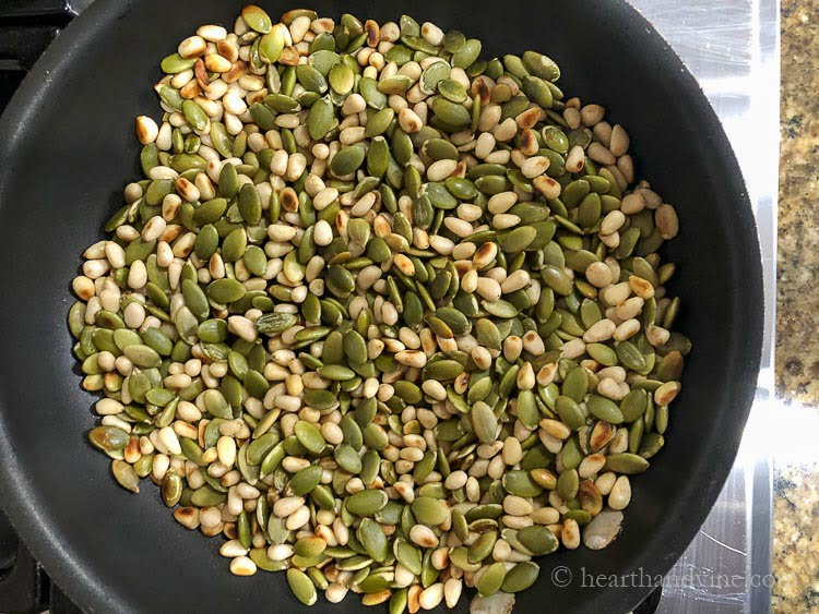 Frying pan with toasted pine nuts and pepito seeds.