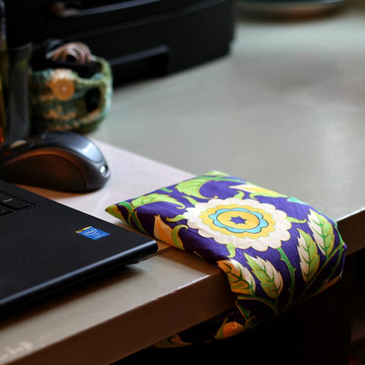 Wrist comfort cuff on desk next to laptop.