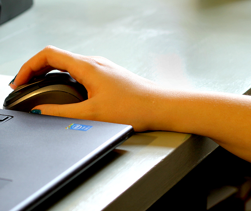 Wrist on edge of desk holding onto mouse.