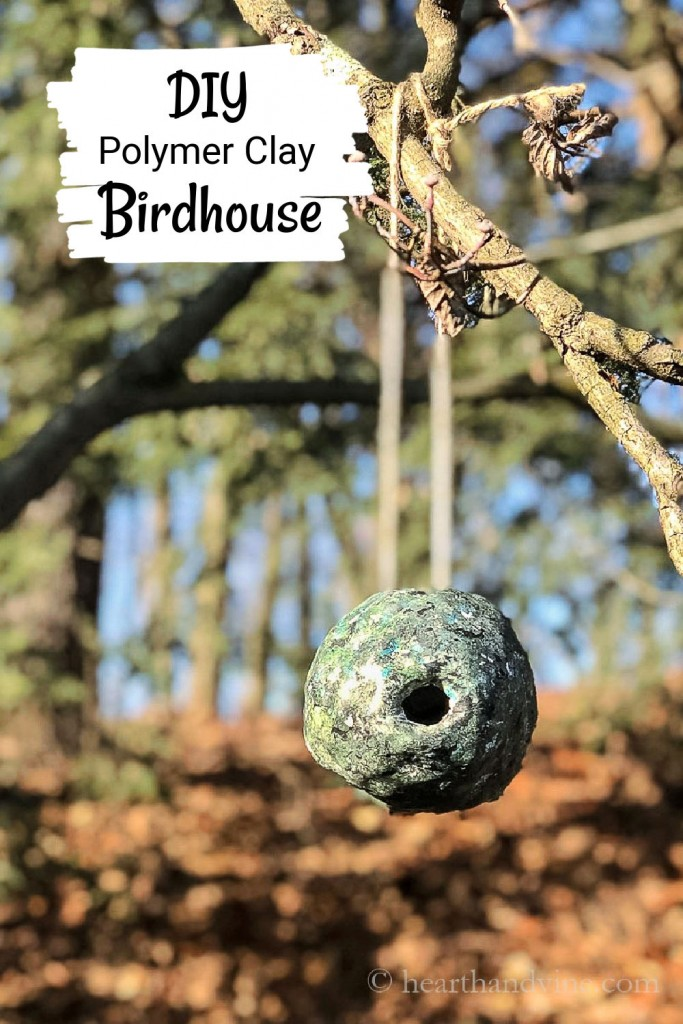 Clay birdhouse hanging from a tree branch.