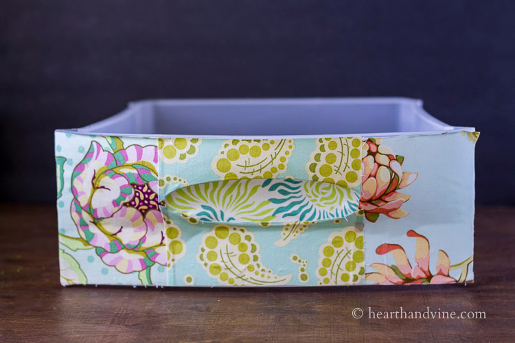 Top drawer of 3 drawer plastic chest with fabric.