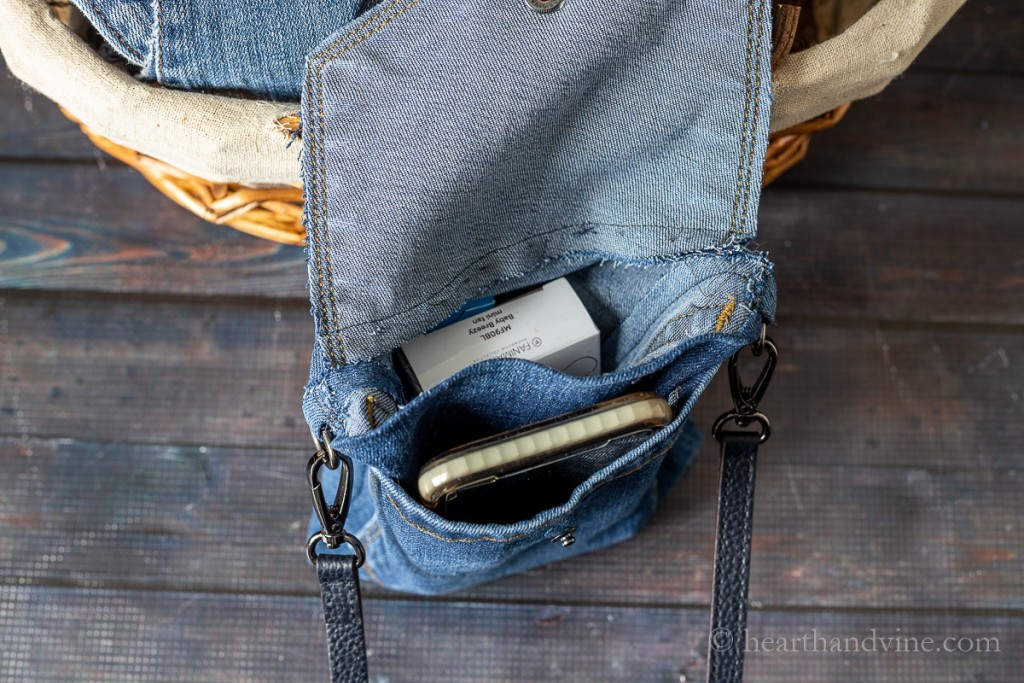 Top of mini jean bag showing inside pockets with a phone and box.