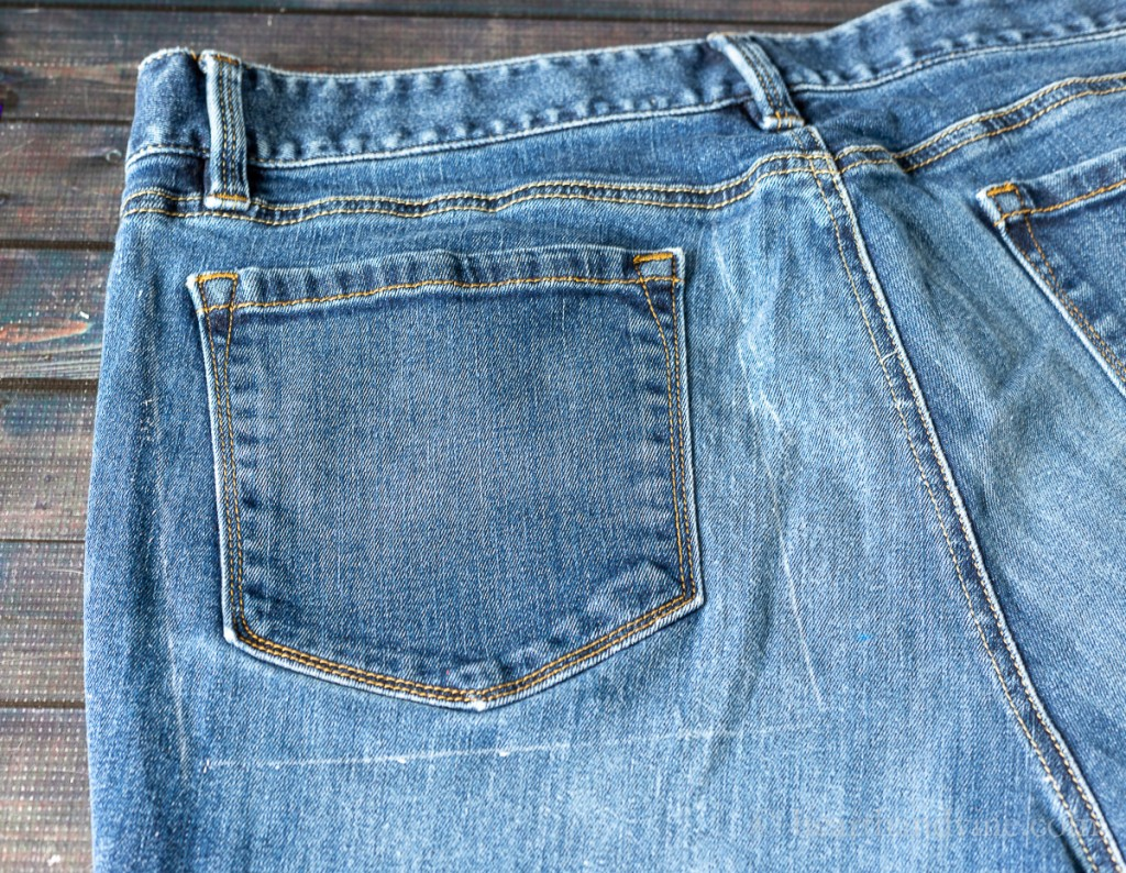 Marked area on back side of blue jeans around a pocket.