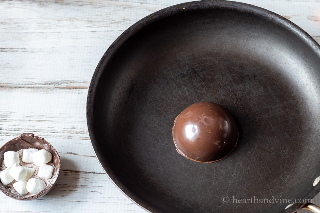 Melting the edge of a chocolate half sphere shell.