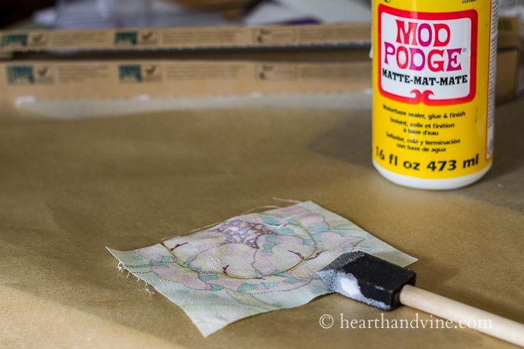 Painting mod podge on the back of a piece of fabric.