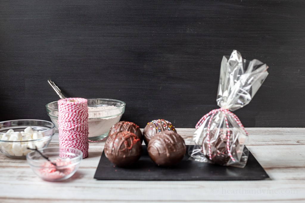 Hot cocoa bombs on a tray, one in a bag, bowls of marshmallows, crushed peppermints and red and white twine.