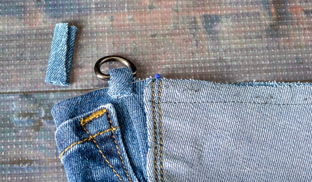 D-ring attached to crossbody bag at top side with strip of denim.