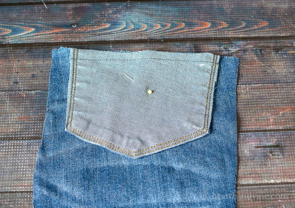 Jean pocket and denim fabric sewn together at top.