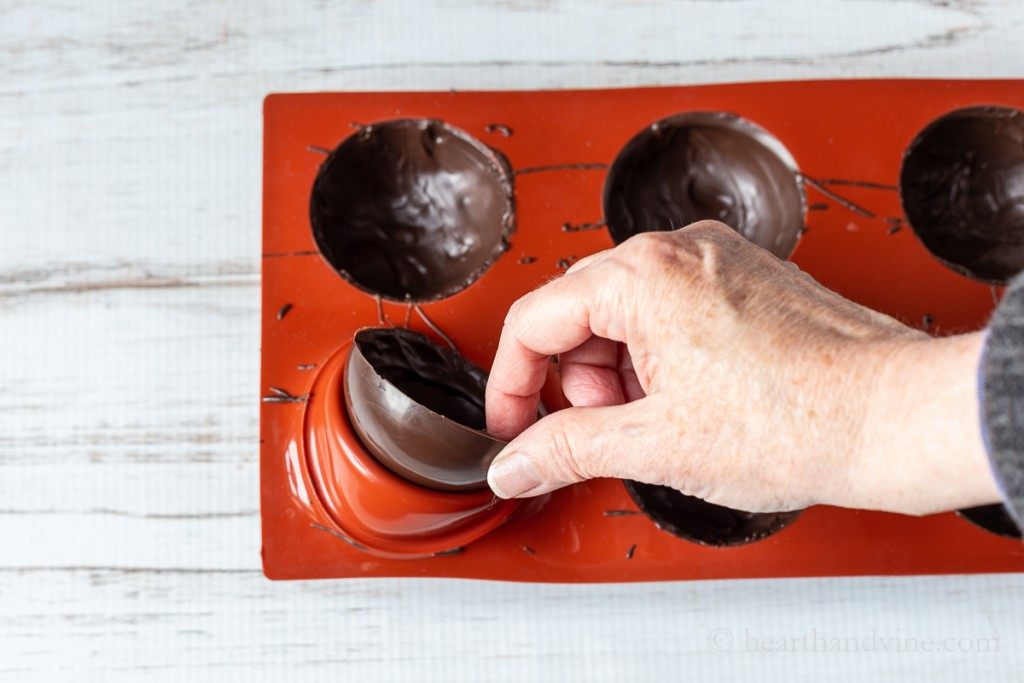 Pulling a chocolate shell from a silicone mold.