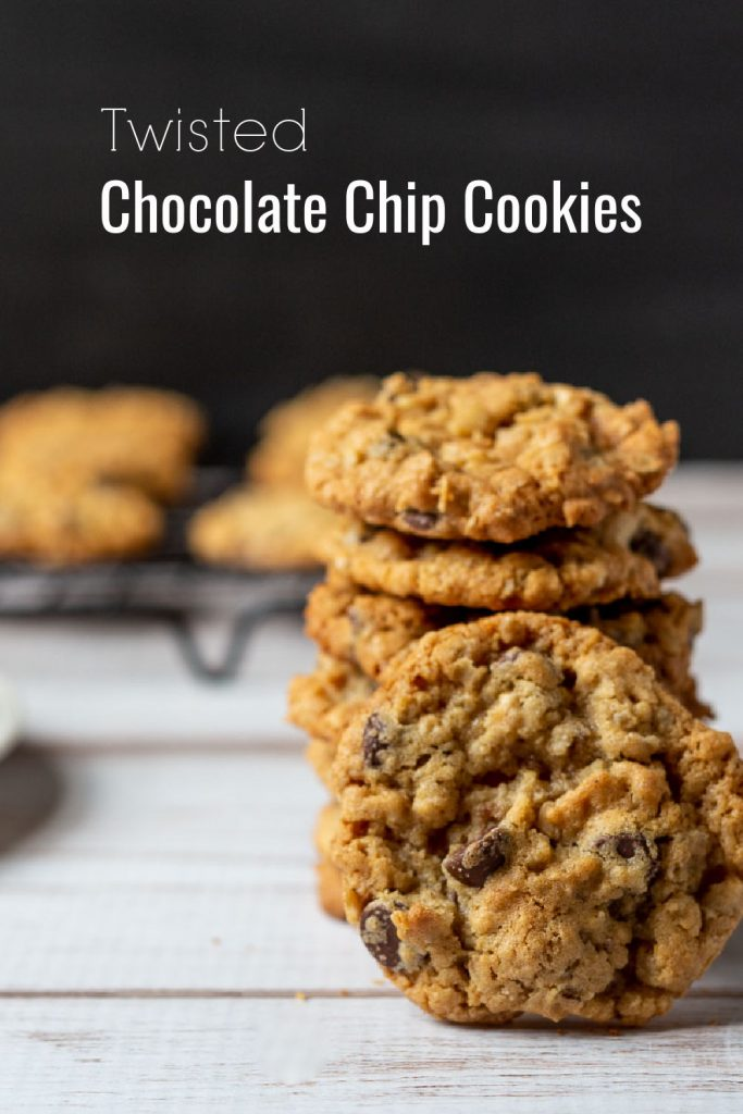 Stack of chocolate chip cookies with one face forward leaning on the stack.