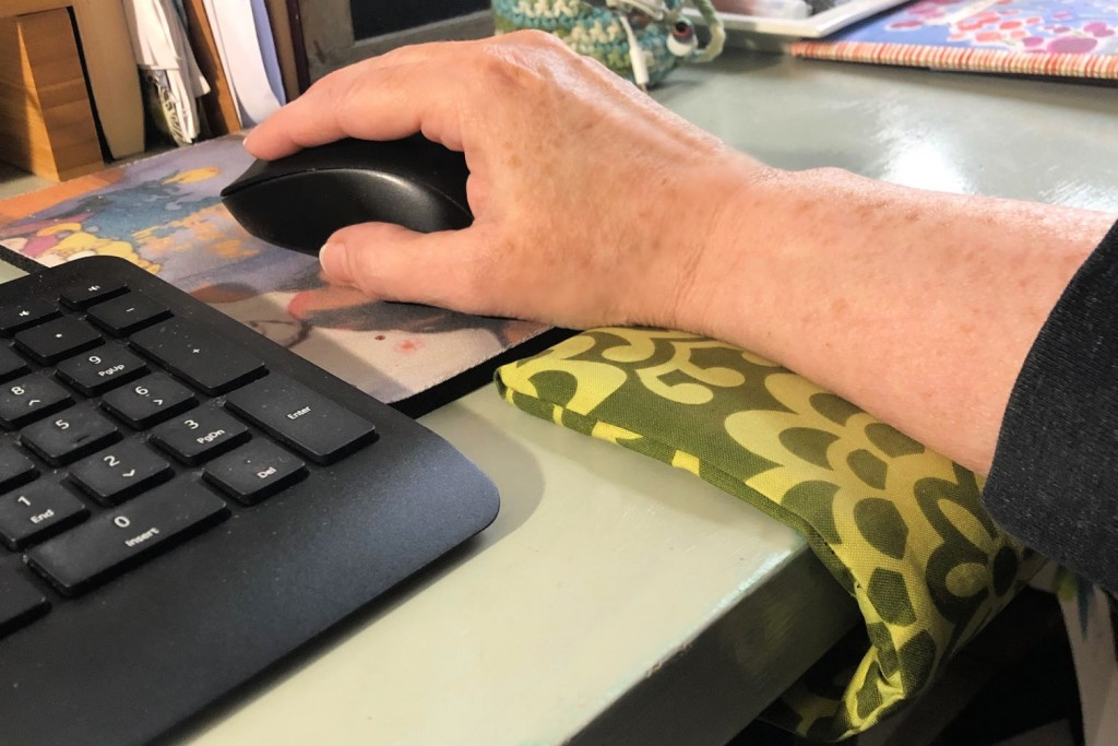 Arm resting on wrist cuff moving a computer mouse.