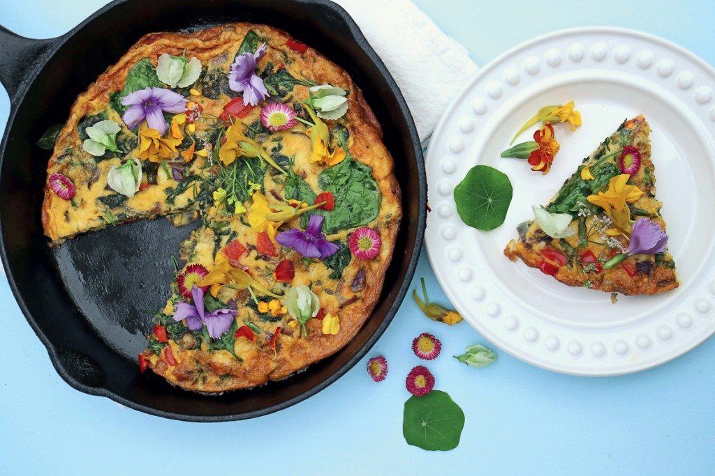 Cast iron skillet with a frittata and edible flowers next to a plate with a piece of the frittata.
