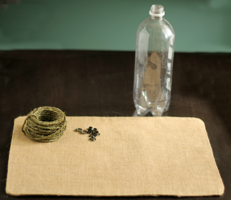 A burlap placemat, green wire, grommets and a plastic water bottle.