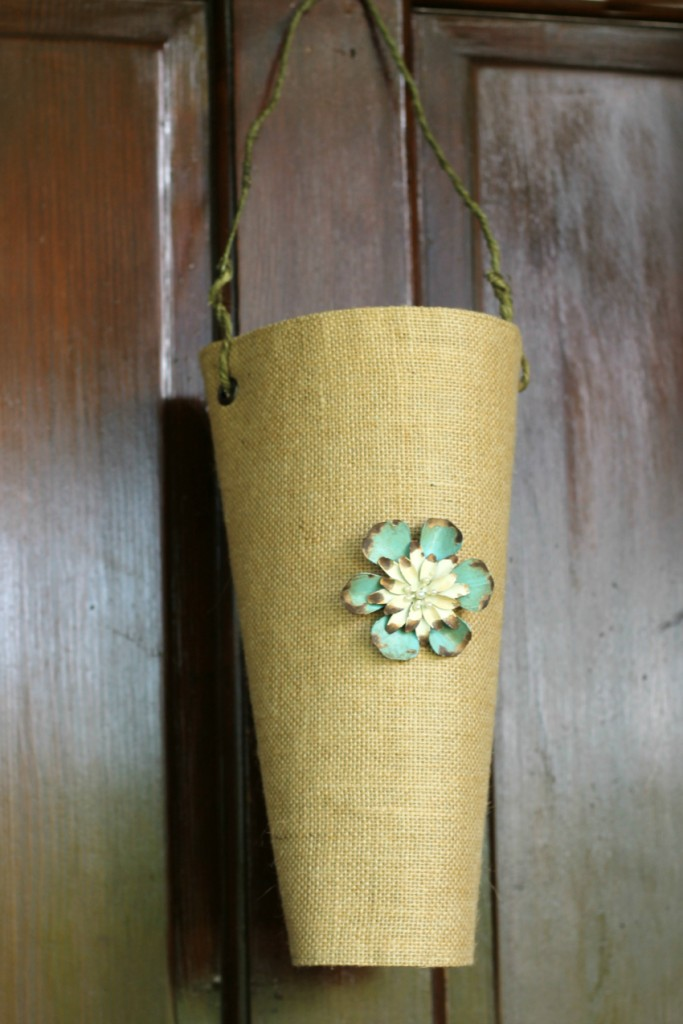 Burlap vase with a blue and cream brooch and a green wire hanger on a door.