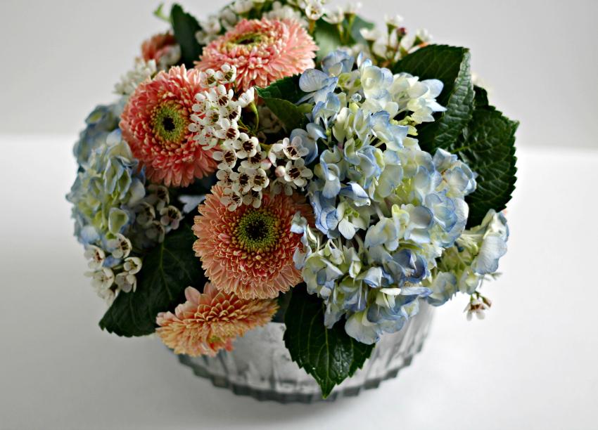 Blue and peach flower arrangement in a mercury glass vase.