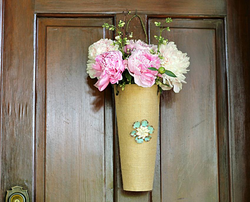 Fresh peonies in a burlap vase hanging on the door.