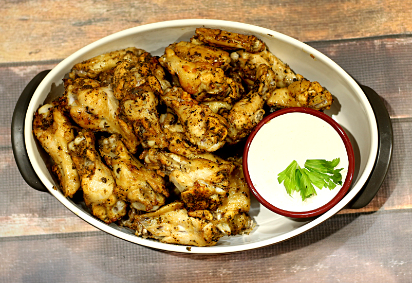Aerial view of baked wings in a serving bowl with a small dish of blue cheese dip.