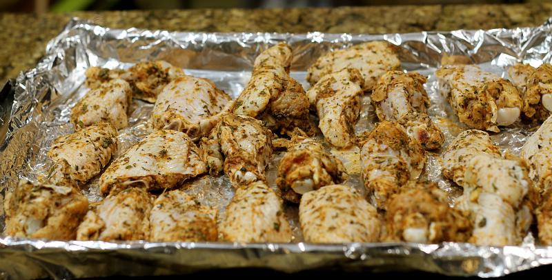 Chicken wings on a foil lined rimmed baking sheet.