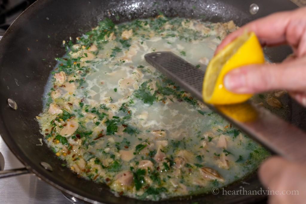 Grating lemon zest to a pan of clam sauce.