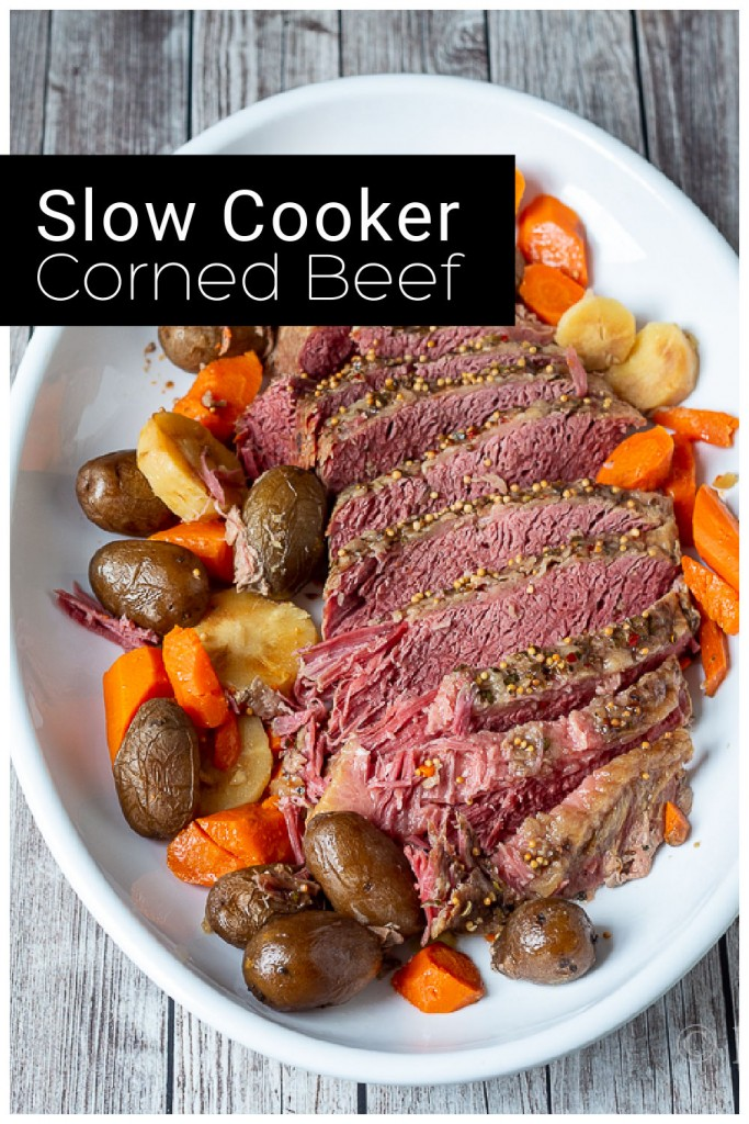 Sliced slow cooker corned beef on a large platter with red potatoes, carrots and parsnips.