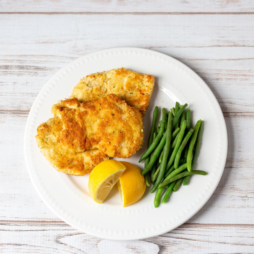 Chicken Romano on a plate with lemon wedges and green beans.