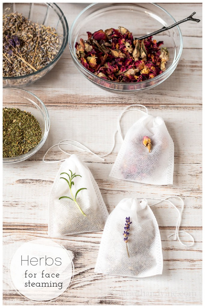 White drawstring teabags. One filled with lavender, one with rosemary and one with rose petals. The bags are lying next to small bowls of dried peppermint, rose petals and lavender.