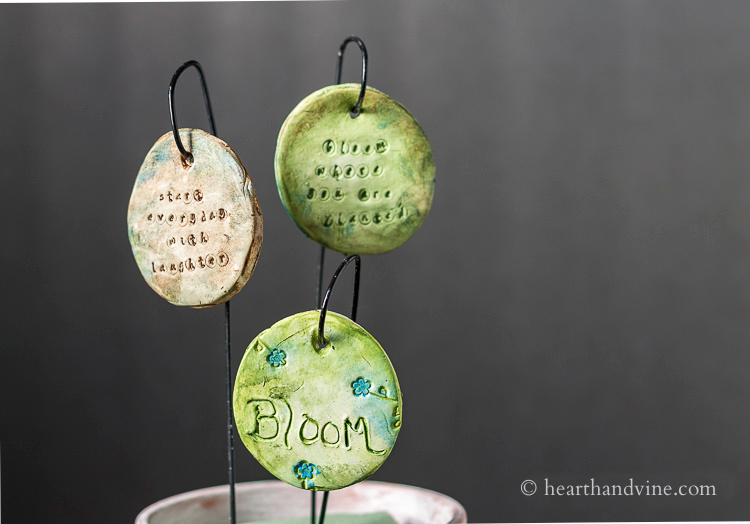 Three garden charms hanging in a clay pot.