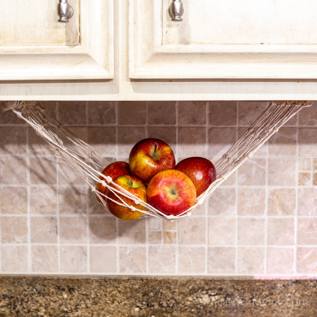 Apples hanging in a fruit hammock under a kitchen cabinet.