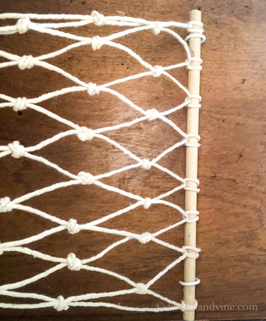 Macrame fruit hammock hung on cup hooks under wood cabinet.