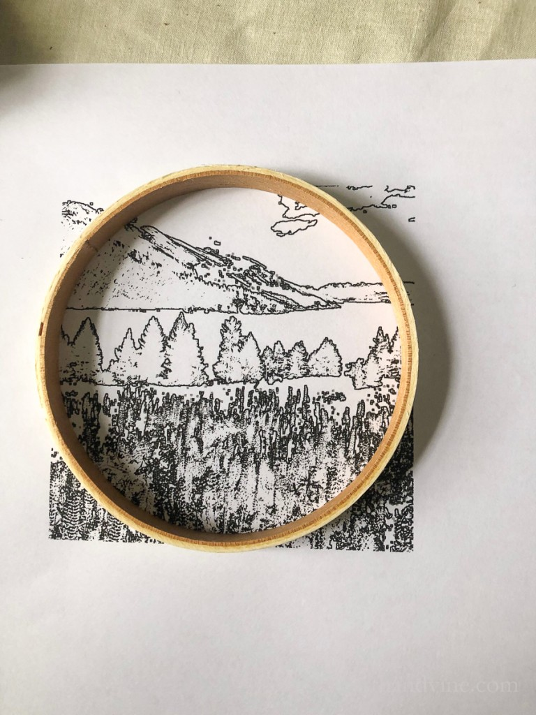 Wooden embroidery hoop covering a black and white landscape drawing.