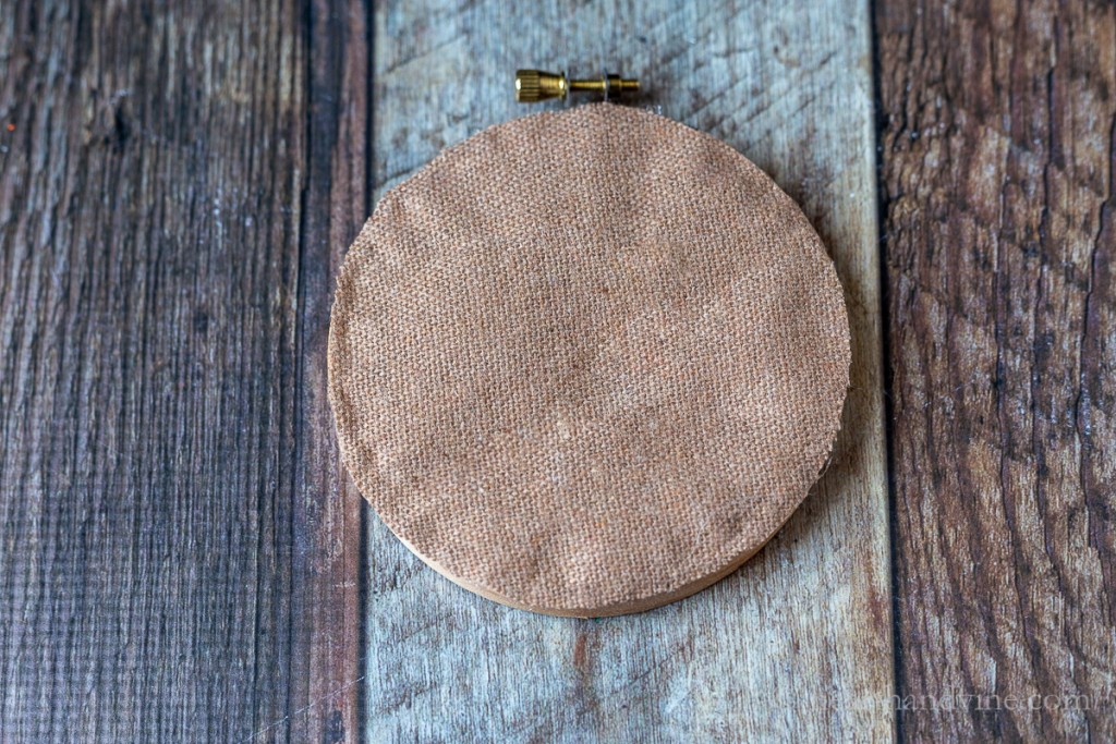 Burlap fabric glued onto back of wooden hoop to finish the craft.
