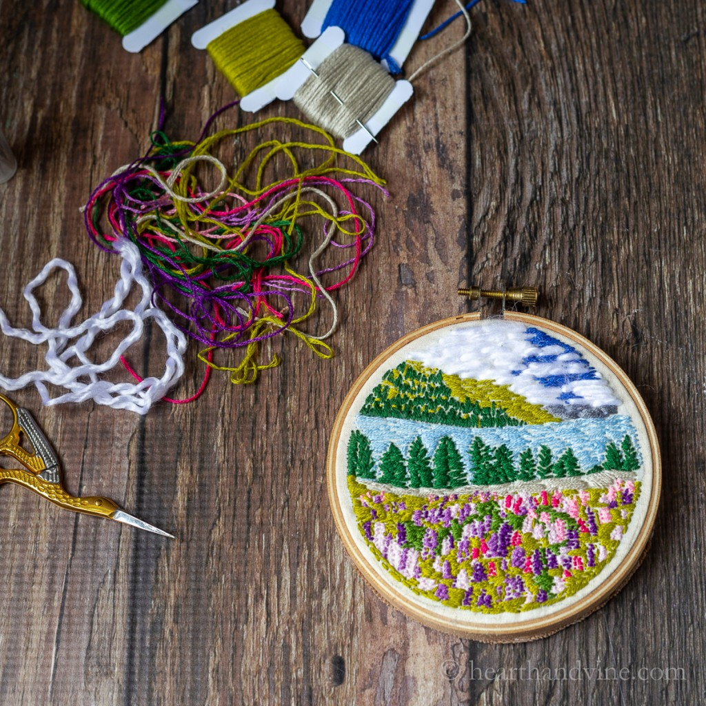Small landscape embroidery art hoop, threads and scissors.