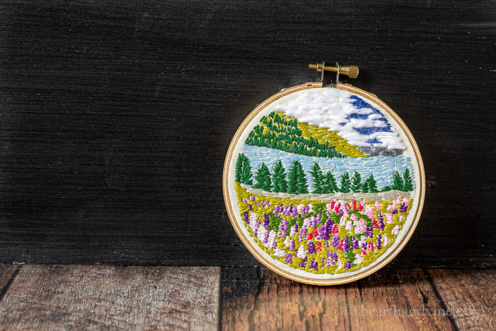 Pretty landscape embroidery art hoop of a lake with mountains in the background, a blue sky with clouds and a lush field of purple and pink flowers in the foreground.