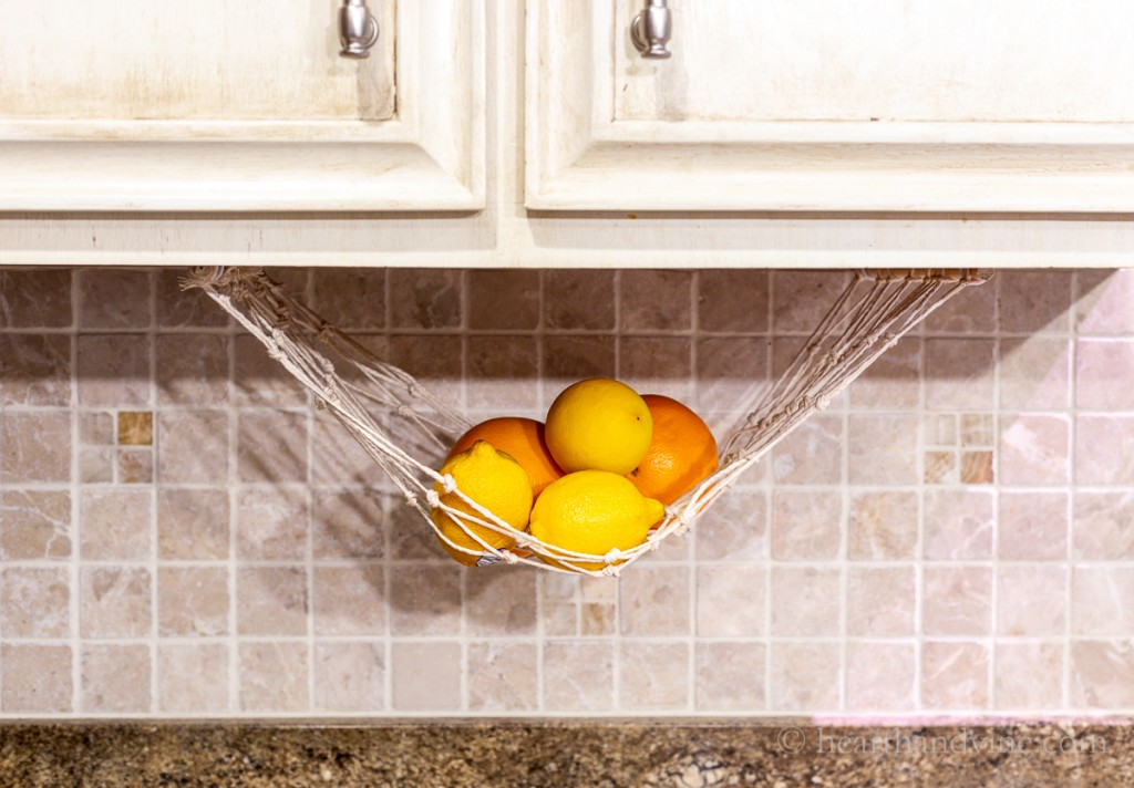 Lemons and oranges hanging in a fruit hammock under a kitchen cabinet.