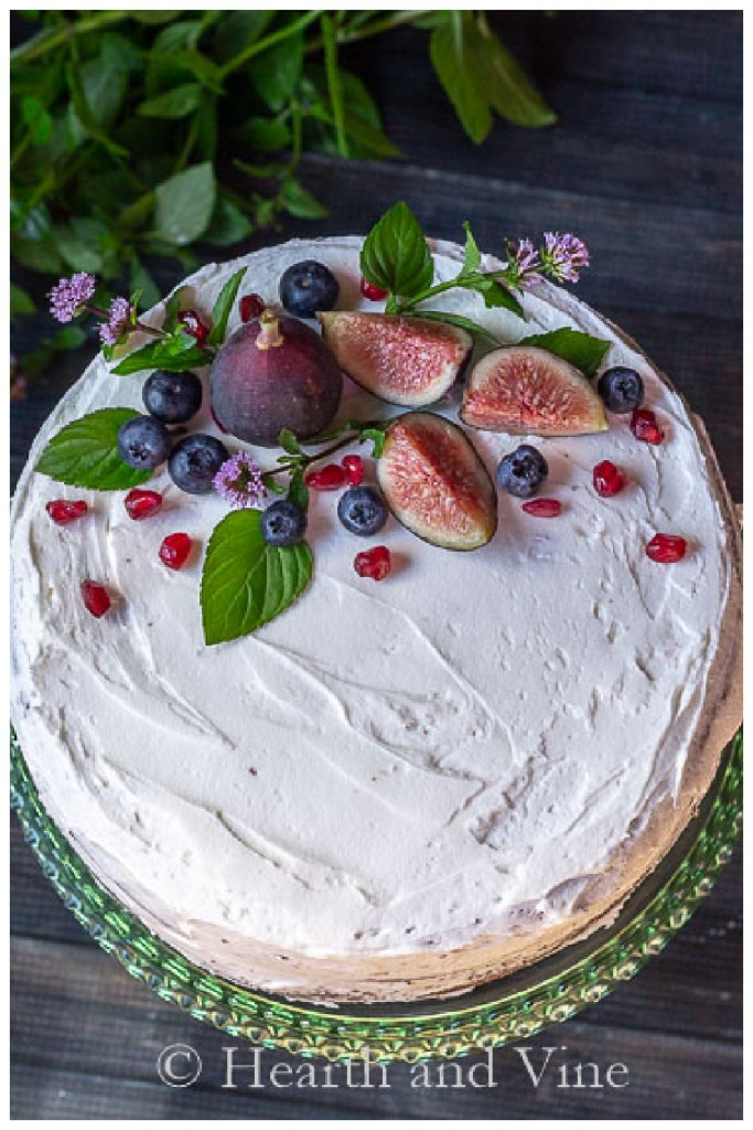 Top view of a naked cake with fruit and fresh mint leaves as decoration.