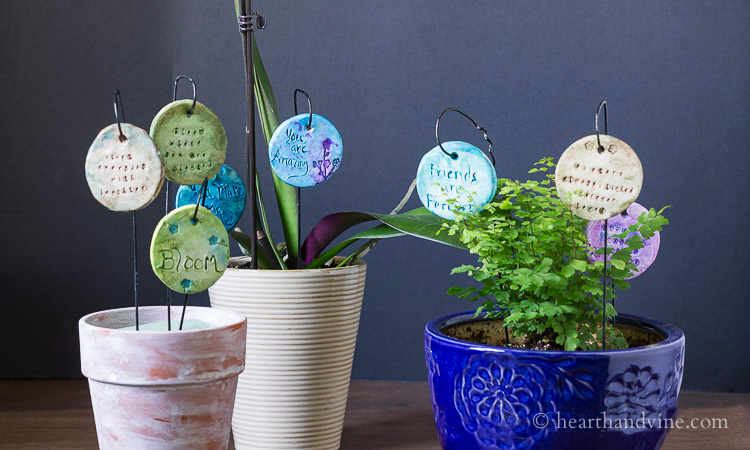 Several pots with garden charms on hangers.
