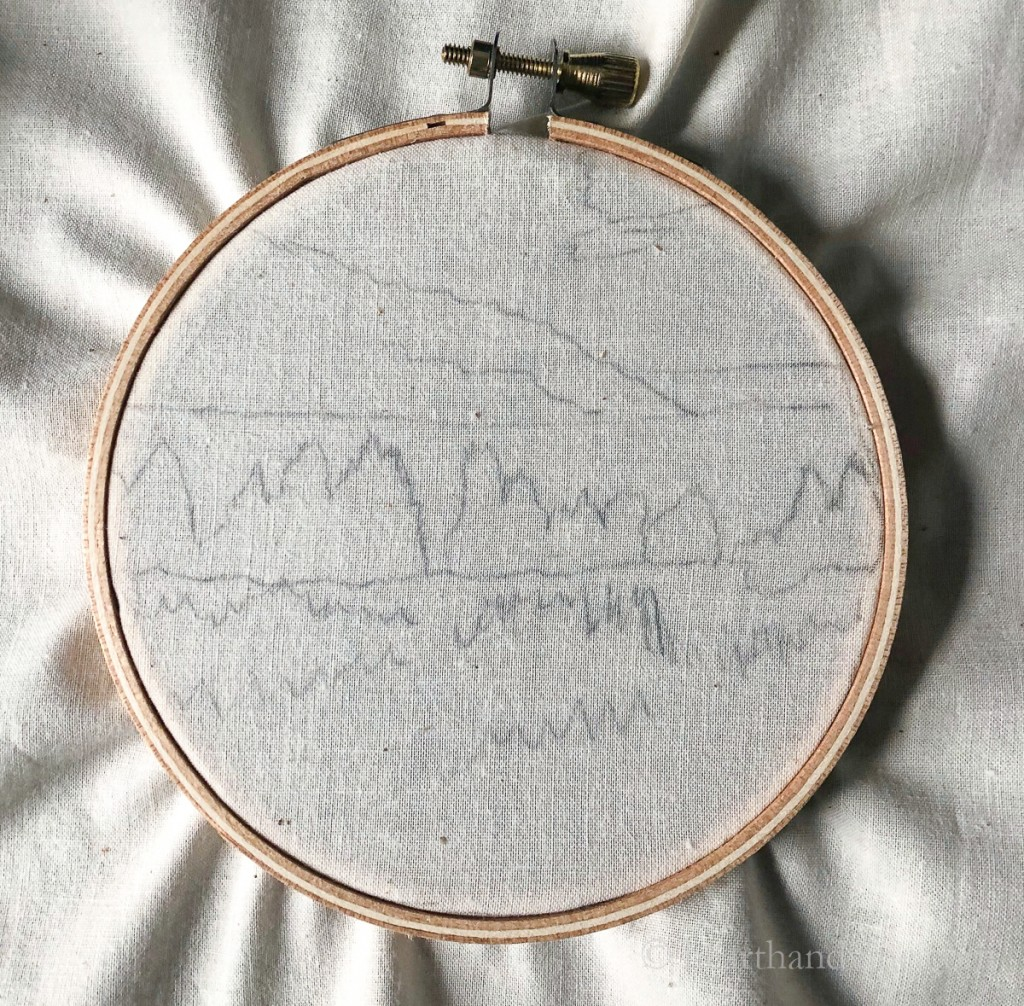 Traced landscape image on muslin in an embroidery hoop.