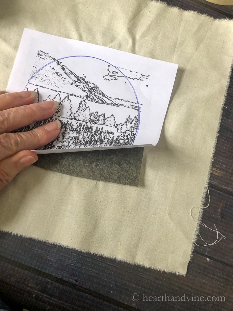 Tracing an image onto muslin with carbon paper.