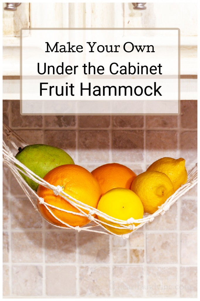 Lemons and oranges hanging in a macrame hammock under a kitchen cabinet.