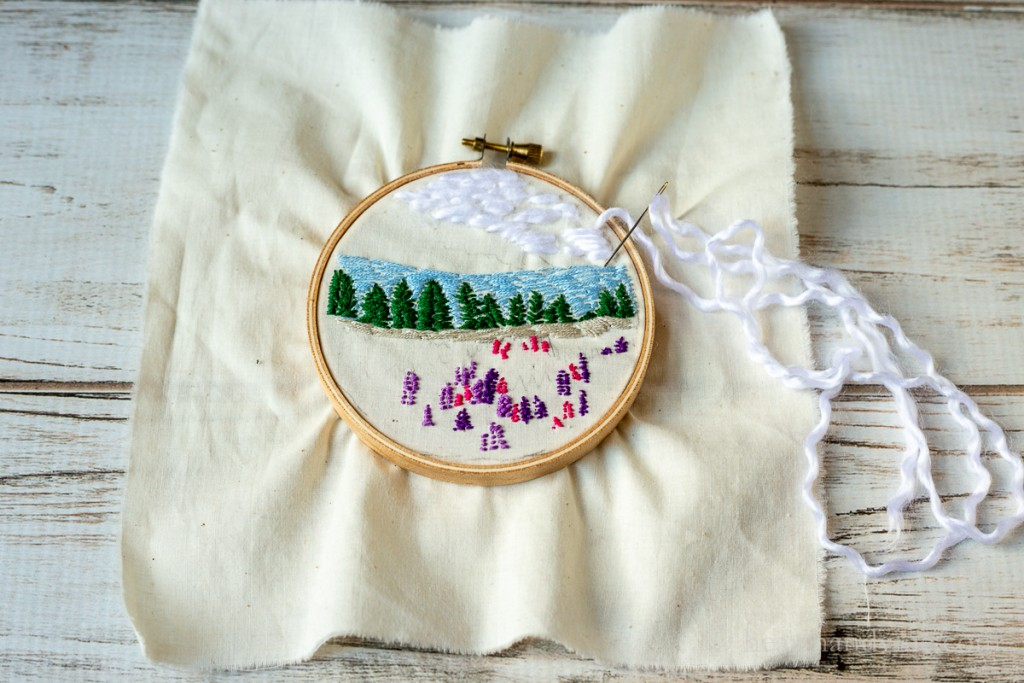 Embroidery hoop and muslin with landscape scene. White yarn creating clouds.