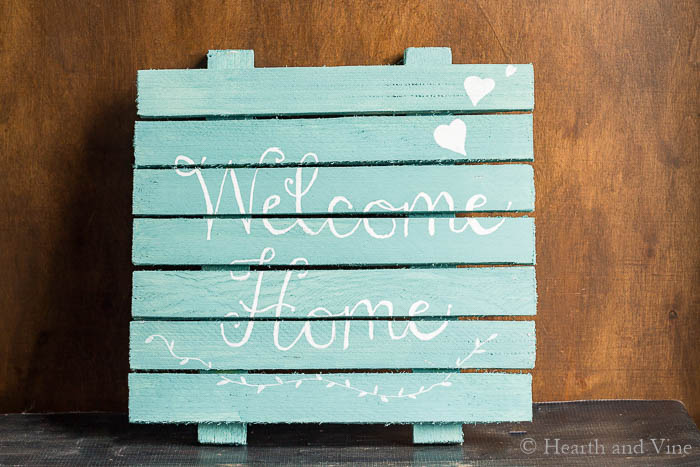 Contractor shims use to create a sign painted aqua with white letters saying Welcome Home.